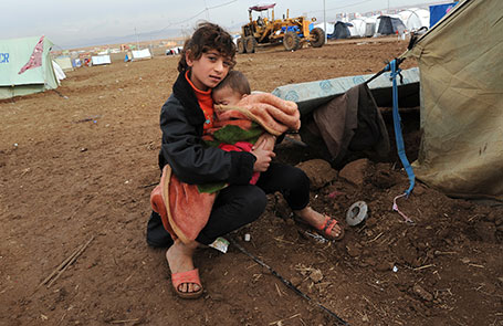 A girl holds a baby on a cold day in a camp for Syrians displaced by civil war
